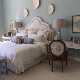 Cette image montre une grand chambre parentale marine avec un mur bleu, un sol en travertin, aucune cheminée et un sol beige.