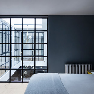 Medium sized urban bedroom in London with light hardwood flooring.