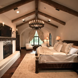 ヒューストンの大きい地中海スタイルのおしゃれな主寝室 (白い壁、濃色無垢フローリング、標準型暖炉、漆喰の暖炉まわり、茶色い床) のレイアウト