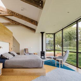 Источник вдохновения для домашнего уюта: спальня в стиле кантри с белыми стенами, паркетным полом среднего тона, печью-буржуйкой, коричневым полом и кроватью у окна