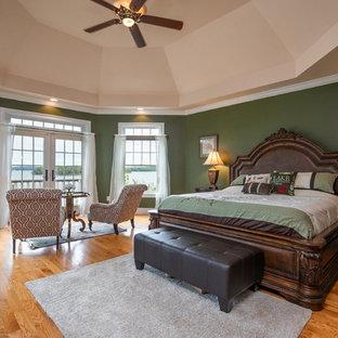 Traditional bedroom in Boston with green walls, medium hardwood floors and brown floor.