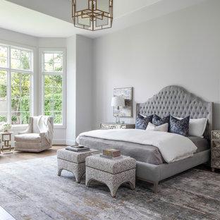 Inspiration för mycket stora klassiska huvudsovrum, med vita väggar, mellanmörkt trägolv, en standard öppen spis och brunt golv