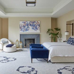 Diseño de dormitorio principal, clásico renovado, grande, con paredes beige, suelo de madera clara, chimenea tradicional, marco de chimenea de hormigón y suelo beige