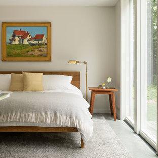 Bedroom - country concrete floor and gray floor bedroom idea in Portland Maine with beige walls