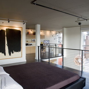 This is an example of an industrial loft-style bedroom in DC Metro with white walls, dark hardwood floors and no fireplace.