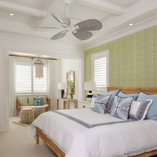 This is an example of a beach style bedroom in Miami with green walls, carpet and beige floor.