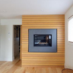 バンクーバーの大きいコンテンポラリースタイルのおしゃれな主寝室 (白い壁、淡色無垢フローリング、標準型暖炉、木材の暖炉まわり) のインテリア