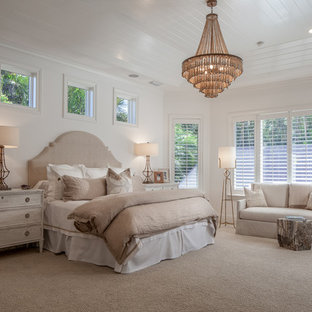Inspiration for a tropical master carpeted and beige floor bedroom remodel in Miami with white walls