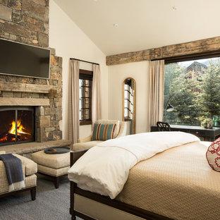 Ejemplo de dormitorio principal, rústico, con paredes blancas, chimenea tradicional y marco de chimenea de piedra
