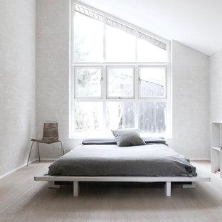 На фото: большая хозяйская спальня в скандинавском стиле с белыми стенами и деревянным полом с