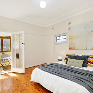 Photo of a large midcentury guest bedroom in Sydney with beige walls, medium hardwood floors, brown floor and no fireplace.