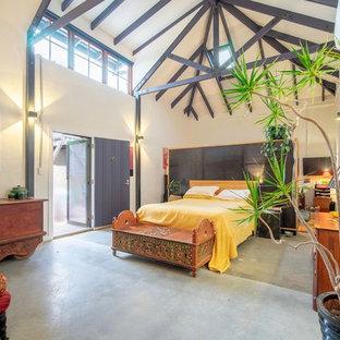 Esempio di una camera da letto boho chic con pareti bianche, pavimento in cemento e pavimento verde