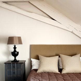 Cette image montre une chambre mansardée ou avec mezzanine rustique de taille moyenne avec un mur blanc.
