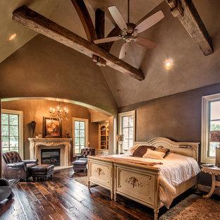 他の地域の広いおしゃれな主寝室 (茶色い壁、濃色無垢フローリング、標準型暖炉、漆喰の暖炉まわり、茶色い床)