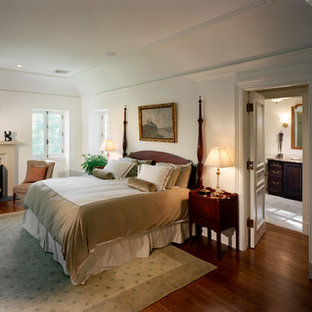 Example of a french country dark wood floor bedroom design in New York with white walls and a standard fireplace