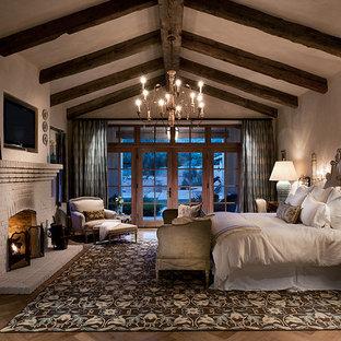Bild på ett medelhavsstil sovrum, med mellanmörkt trägolv, en standard öppen spis, en spiselkrans i tegelsten och grå väggar