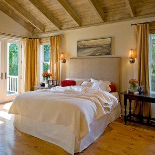 Immagine di una camera da letto chic con pareti beige, pavimento in legno massello medio e pavimento giallo