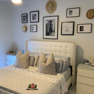 Modelo de dormitorio tipo loft y abovedado, de estilo de casa de campo, pequeño, con paredes blancas, suelo de baldosas de porcelana y suelo blanco