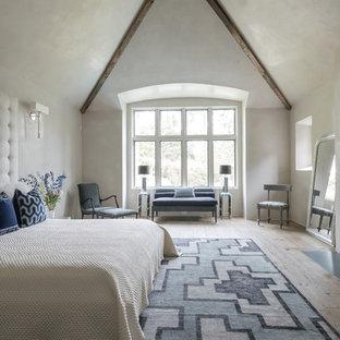 Imagen de dormitorio principal, campestre, grande, con paredes blancas, suelo de madera clara, chimenea lineal y suelo beige