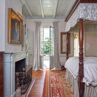 Idee per una camera da letto classica con camino classico e pavimento arancione