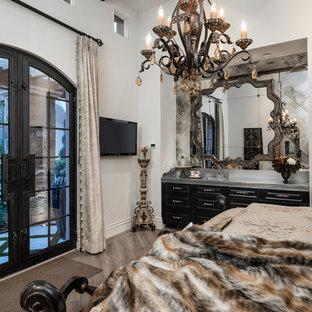 Immagine di un'ampia camera degli ospiti stile shabby con pareti bianche, parquet scuro, camino bifacciale, cornice del camino in pietra e pavimento marrone