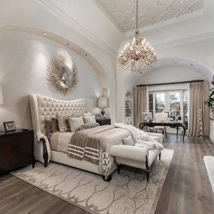 Imagen de dormitorio principal, mediterráneo, extra grande, con paredes blancas, suelo de madera oscura, chimenea de doble cara, marco de chimenea de piedra y suelo marrón