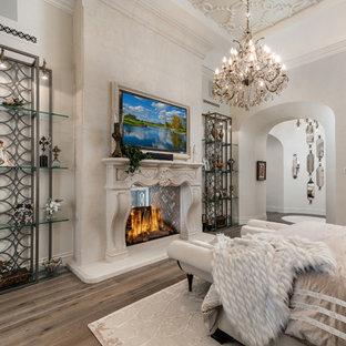 Modelo de dormitorio principal, mediterráneo, extra grande, con paredes blancas, suelo de madera oscura, chimenea de doble cara, marco de chimenea de piedra y suelo marrón