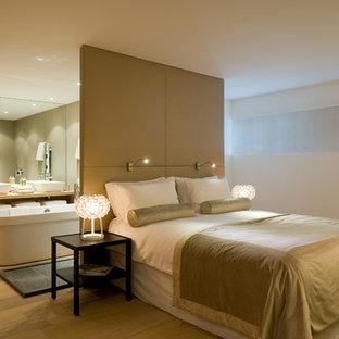 Cette image montre une grande chambre parentale design avec un mur blanc et un sol en bois clair.