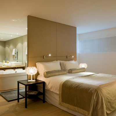 Example of a large trendy master light wood floor bedroom design in Other with white walls