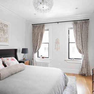 Large transitional master light wood floor and brown floor bedroom photo in New York with gray walls