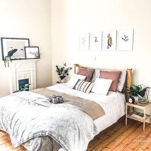 エディンバラの中くらいの北欧スタイルのおしゃれな主寝室 (白い壁、淡色無垢フローリング、標準型暖炉、漆喰の暖炉まわり、茶色い床) のレイアウト