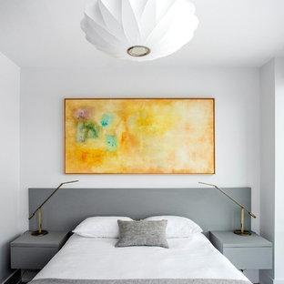 Foto de dormitorio principal, minimalista, pequeño, con paredes blancas, suelo laminado y suelo marrón