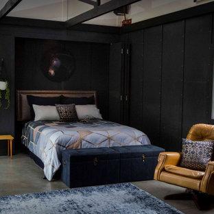 Imagen de habitación de invitados boiserie, urbana, grande, con paredes negras, suelo de cemento, suelo gris y boiserie