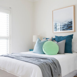 Large beach style guest bedroom in Sydney with carpet, beige floor and white walls.