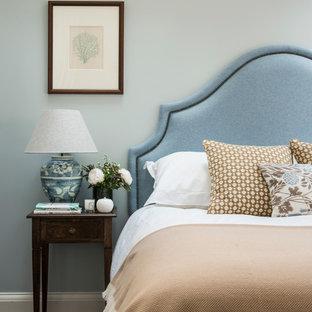 Modelo de dormitorio principal, clásico, de tamaño medio, con paredes azules y suelo de madera oscura