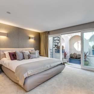 Design ideas for a medium sized contemporary master bedroom in London with beige walls, carpet, no fireplace and beige floors.