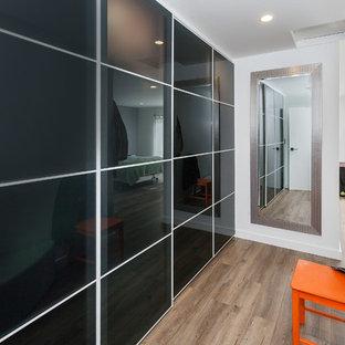 ロサンゼルスの中くらいのコンテンポラリースタイルのおしゃれな主寝室 (黒い壁、淡色無垢フローリング、暖炉なし、コンクリートの暖炉まわり、茶色い床) のインテリア