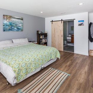 Foto de dormitorio principal, actual, grande, sin chimenea, con paredes blancas, suelo de madera en tonos medios, marco de chimenea de hormigón y suelo marrón