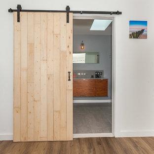 ロサンゼルスの広いコンテンポラリースタイルのおしゃれな主寝室 (白い壁、無垢フローリング、暖炉なし、コンクリートの暖炉まわり、茶色い床) のインテリア