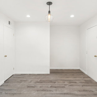 Example of a mid-sized transitional master laminate floor and brown floor bedroom design in San Francisco with gray walls and no fireplace