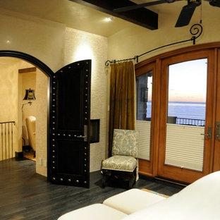 Foto di una camera matrimoniale chic di medie dimensioni con pareti gialle, parquet scuro, camino lineare Ribbon e cornice del camino in pietra