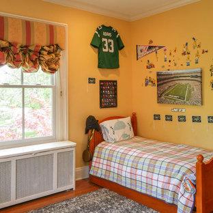 Modelo de dormitorio de tamaño medio, sin chimenea, con paredes amarillas, suelo de madera en tonos medios y suelo multicolor