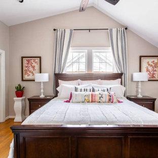 Modelo de habitación de invitados clásica renovada, de tamaño medio, con paredes beige, suelo de madera en tonos medios y suelo naranja