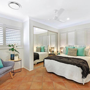 Design ideas for a mid-sized beach style guest bedroom in Gold Coast - Tweed with grey walls and terra-cotta floors.