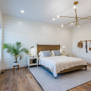 Example of a cottage guest medium tone wood floor and brown floor bedroom design in Other with white walls