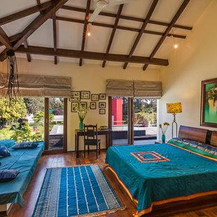 Esempio di una camera da letto tropicale con pareti beige e parquet scuro