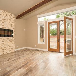 Esempio di una camera matrimoniale contemporanea con pareti grigie, pavimento in legno massello medio, camino sospeso, cornice del camino in pietra e pavimento grigio