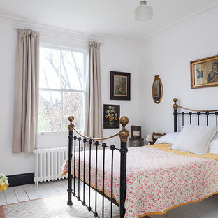 Photo of a medium sized traditional bedroom in London with white walls, painted wood flooring, white floors and a standard fireplace.