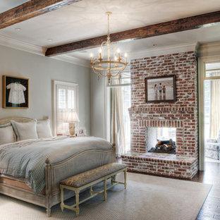 Inredning av ett klassiskt mellanstort huvudsovrum, med grå väggar, mellanmörkt trägolv, en spiselkrans i tegelsten och en dubbelsidig öppen spis