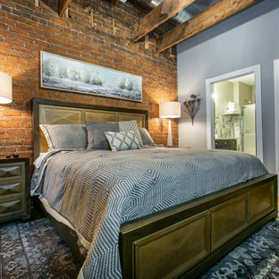 Inspiration for an industrial bedroom in Chicago with grey walls, medium hardwood floors, brown floor, exposed beam and brick walls.